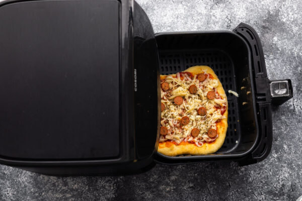 overhead view of uncooked pizza in air fryer
