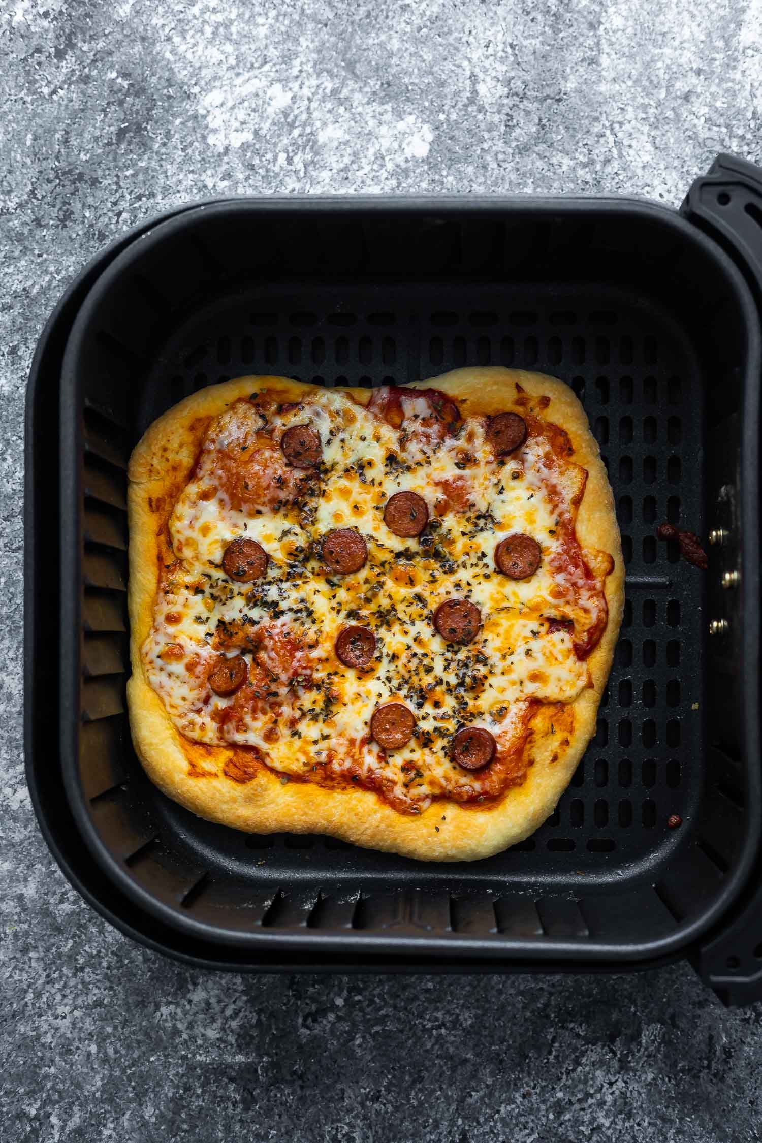 overhead view of cooked pizza in air fryer basket