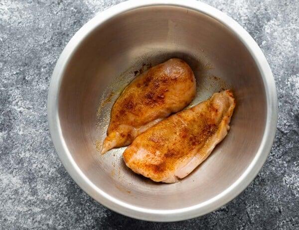 chicken breasts in silver bowl tossed in seasonings
