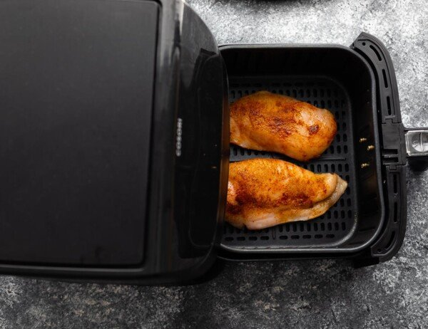 chicken breasts in air fryer basket before cooking