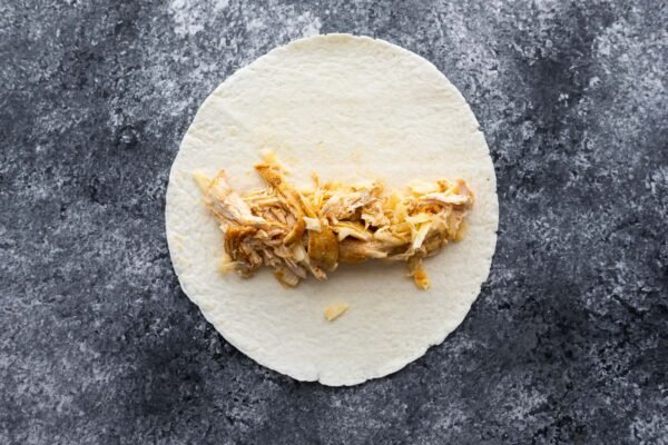 shredded chicken and cheese on a tortilla