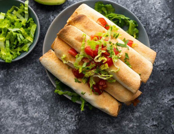 cooked taquitos stacked on a plate, topped with lettuce and tomatoes