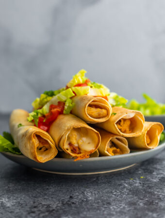 side angle view of plate stacked with taquitos