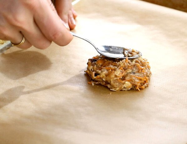 patting the breakfast cookie onto a parchment-lined baking sheet with a spoon