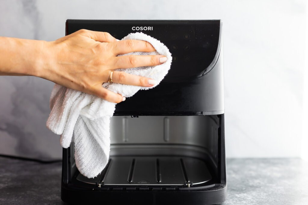 wiping the outside of the air fryer basket model with a damp cloth