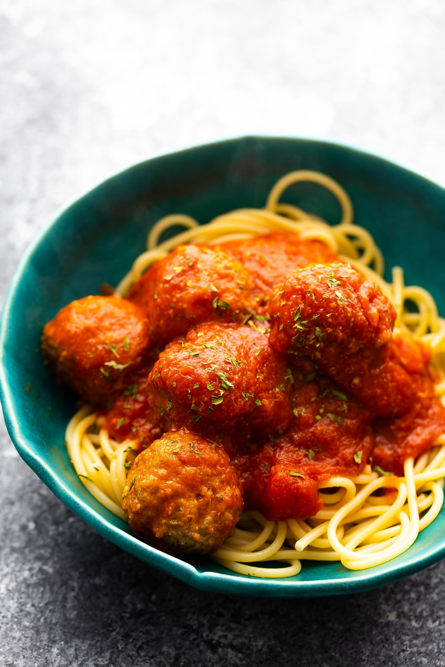 close up shot of meatballs on a bed of. spaghetti in blue bowl