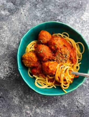 bowl of spaghetti and meatballs with one meatball broken open and spaghetti wound around a fork