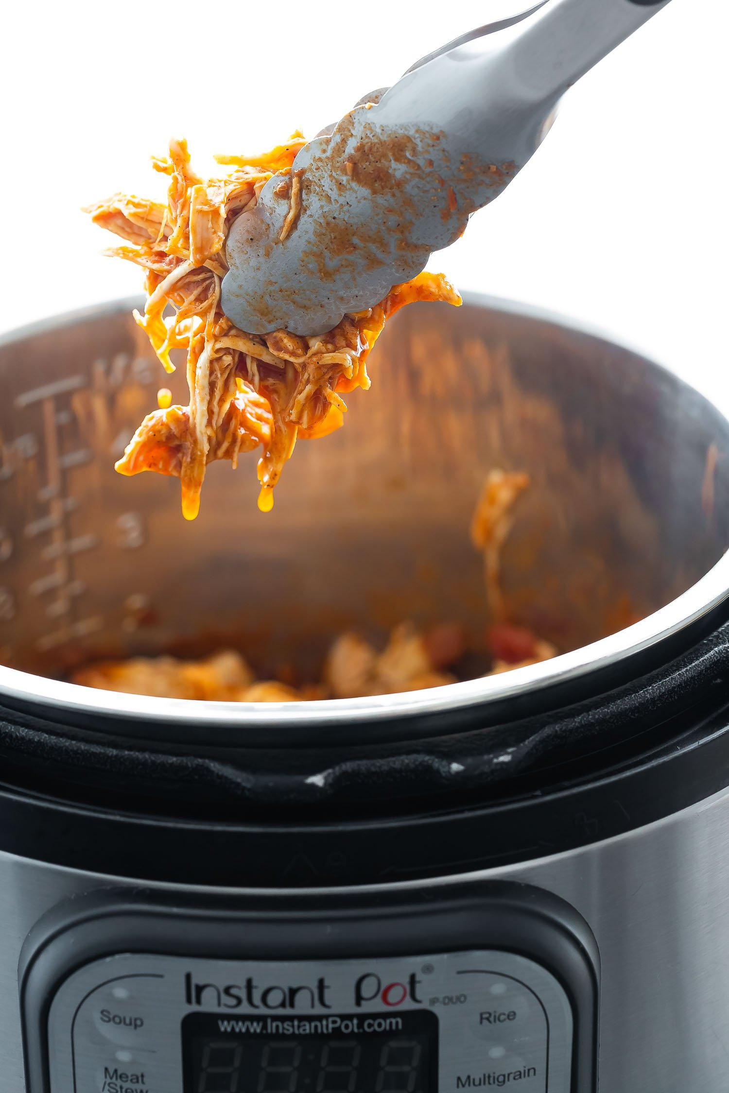 close up shot of salsa chicken pulled out of Instant Pot with tongs