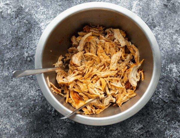 overhead view of shredded chicken in bowl with two forks