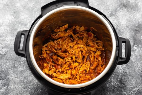 overhead view of shredded salsa chicken in the instant pot after cooking through