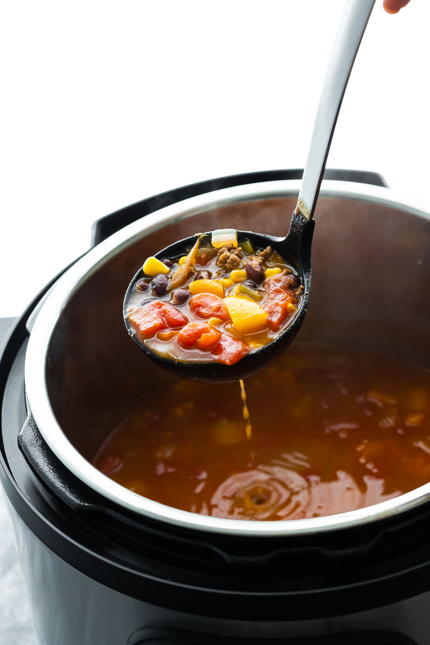 taco soup scooped up in ladle above the instant pot