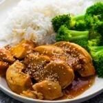 close up view of chicken teriyaki on white plate with broccoli and rice