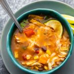 chicken tortilla soup in blue bowl with spoon