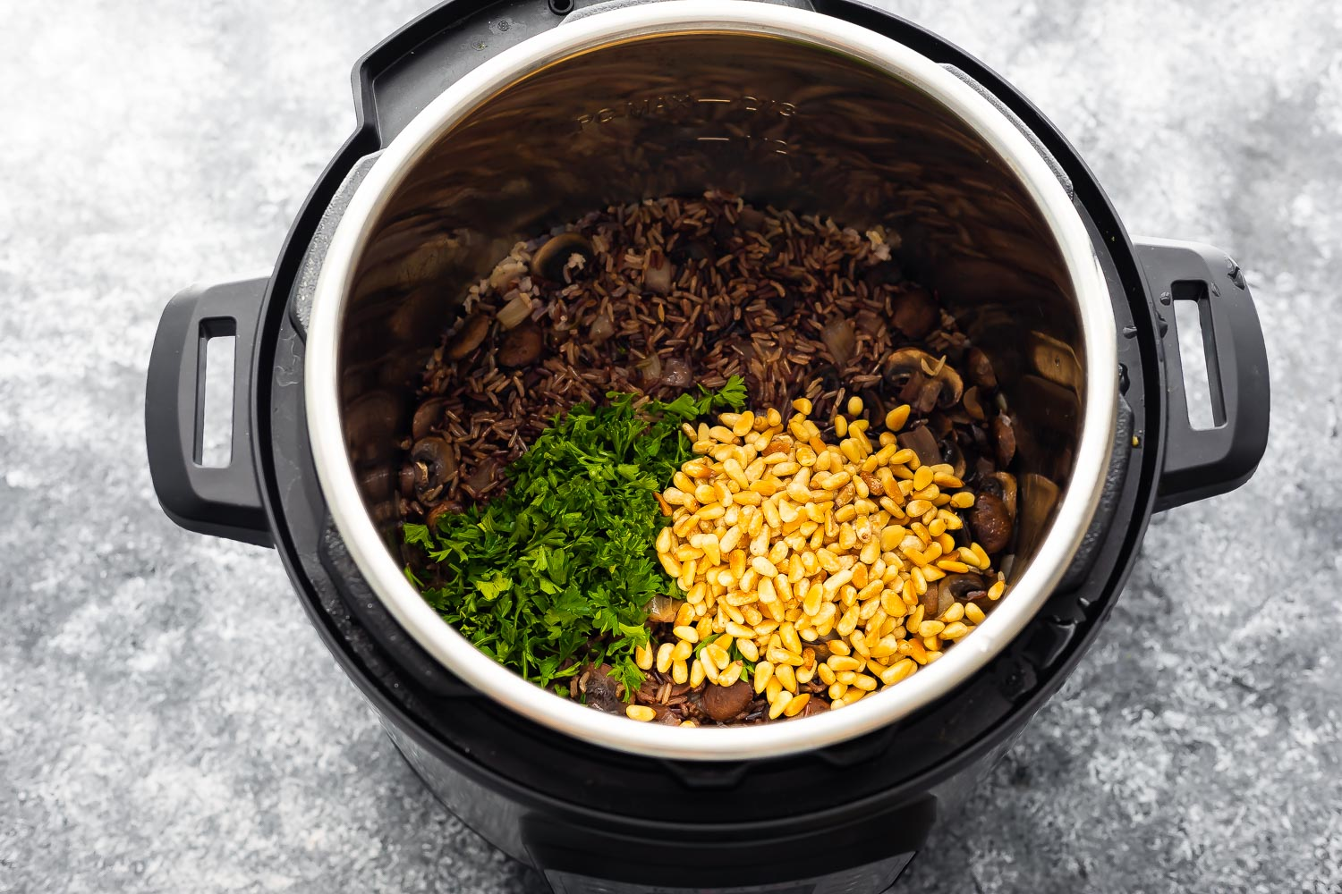 stirring parsley and pine nuts into the instant pot wild rice pilaf