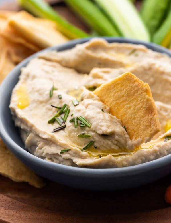 close up view of pita chip in white bean dip