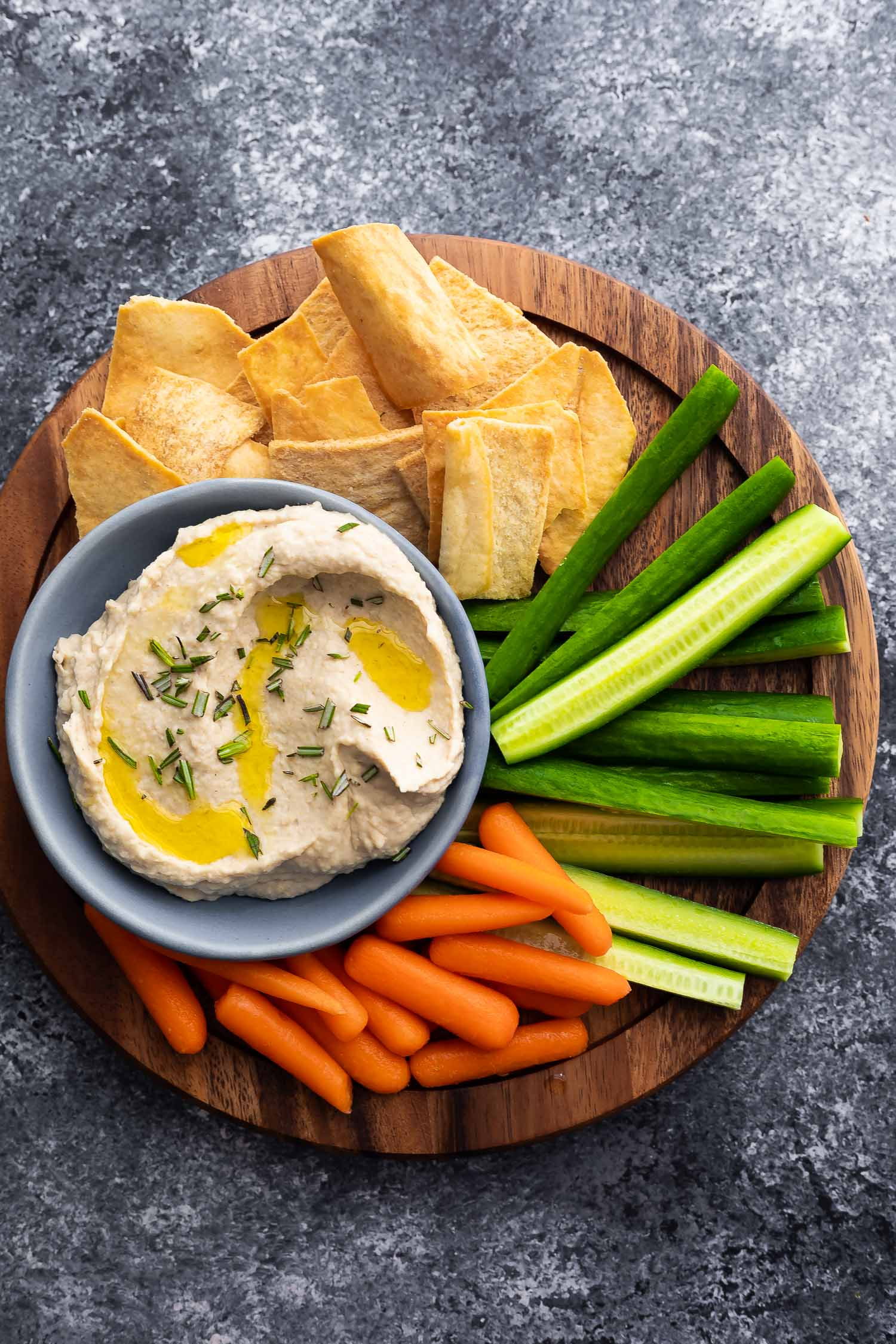 white bean dip on platter with vegetables and pita chips