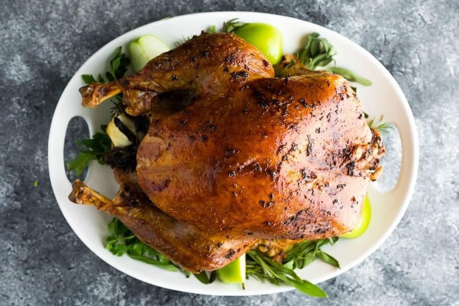 overhead shot of a cooked turkey with garlic sage butter on a white platter with fresh herbs