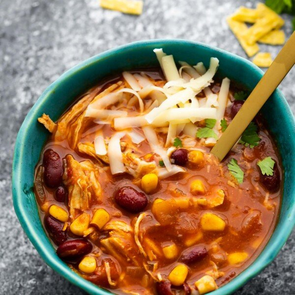 chicken chili in blue bowl topped with cheese