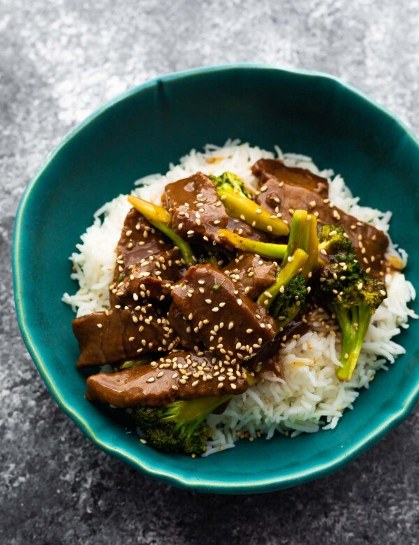 beef and broccoli served over rice in blue bowl