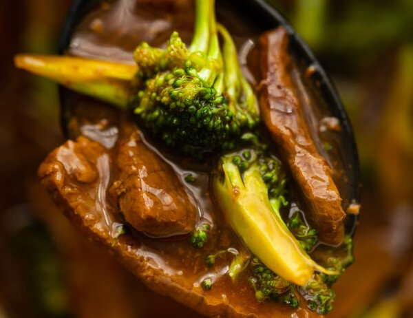 close up shot of beef and broccoli on a spoon