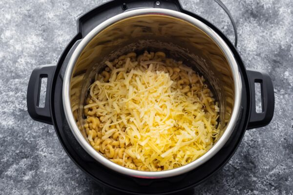overhead view of cheese added to macaroni in the instant pot