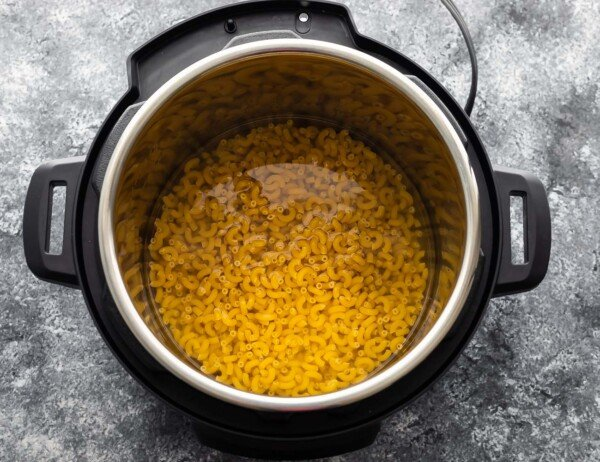 macaroni and water in the instant pot before cooking through
