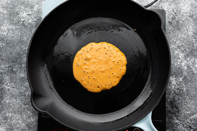 pumpkin pancake cooking in black pan