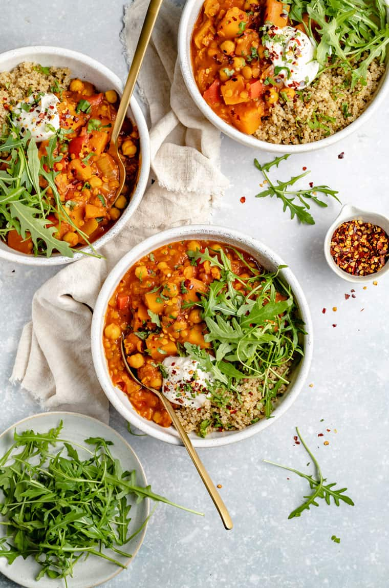overhead of three bowls of moroccan chickpea stew with quinoa, arugula and butternut squash