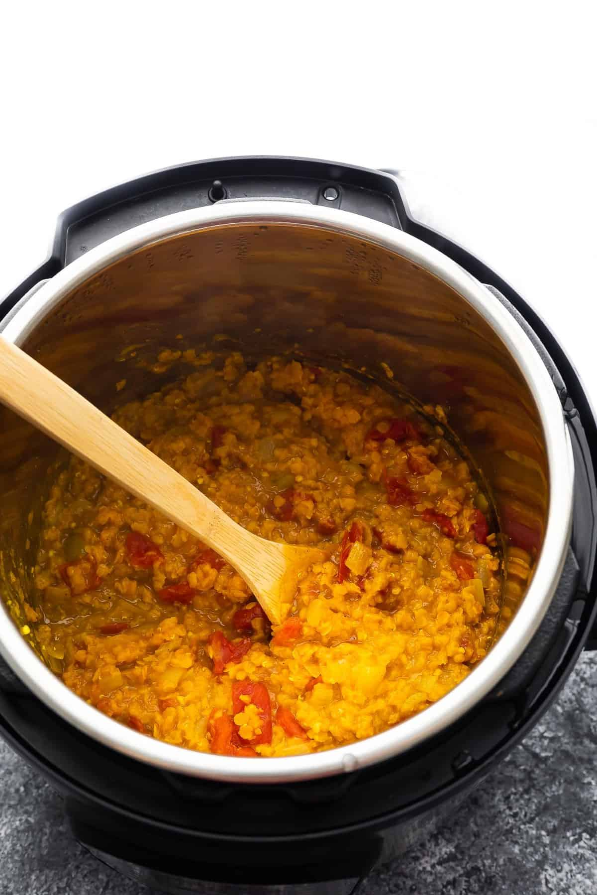 cooked dal in instant pot with wooden spoon