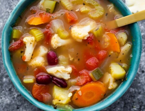 vegetable soup in blue bowl with spoon